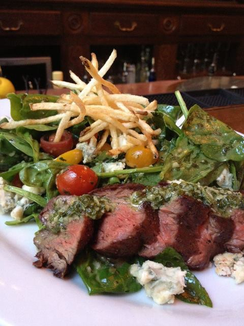 A colorful, vibrant plate of Hangar steak, spinach salad, and frites.