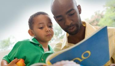 A father reads to his son.